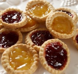Selection of homemade jam tarts on a white plate